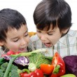 Two little boys eating vegetables — Stock Photo