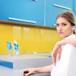 Young beautiful blonde woman in kitchen sitting on chair — Stock Photo #26232233