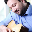 Man playing guitar and relaxing at home — Stock Photo