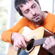 Male adult playing guitar — Stock Photo