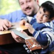 Father and son playing guitar at home — Stock Photo #26238707
