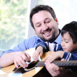 Father and son playing guitar at home — Stock Photo #26238909