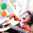 Kid singing and playing guitar at home — Stock Photo