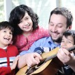 Happy family playing guitar together at home — Stock Photo