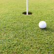 Golf ball at hole on grass field — Stok fotoğraf