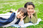 Two children laying on grass, brother and sister — Stock Photo