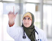Muslim female doctor pressing digital Enter button — Stock Photo