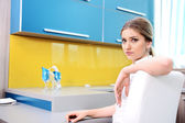 Young beautiful blonde woman in kitchen sitting on chair — Stock Photo