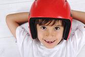 Pouco bonito rapaz com capacete na cabeça deitado relaxado — Foto Stock