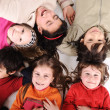 Children group in circle laying on ground — Stock Photo #26243599
