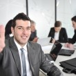 Portrait of young businessman in the office with thumb up — Stock Photo