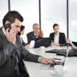 Business mspeaking on phone and typing on laptop while in meeting — Stok Fotoğraf #26246357