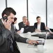Business mspeaking on phone and typing on laptop while in meeting — Zdjęcie stockowe #26246357