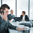 Business man speaking on the phone while in a meeting — Stock Photo #26246359