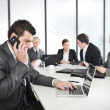 Businessman calling on phone, business meeting at background — 图库照片