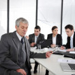 Senior businessman at a meeting. Group of colleagues in the background — Stock Photo #26246603