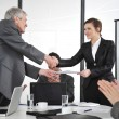 Business partners handshaking at meeting and receiving applause — Stock Photo
