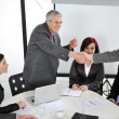 Successful business colleagues shaking hands with eachother at meeting - Stock Photo