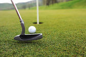 Golf ball and stick on green grass — Stock Photo