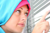 Muslim girl looks out of the window through a jalousie — Stock Photo