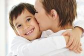 счастливая мать обнимая и целуя ее сына — Стоковое фото