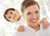 Portrait of young mother piggybacking her son indoor — Stock Photo