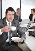 Businessman in business ambience drinking cofee — Stock Photo