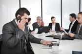 Affärsman tala i telefon och att skriva på laptop medan i ett möte — Stockfoto