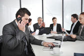 Hombre de negocios hablando por teléfono y escribiendo en la laptop mientras que en una reunión — Foto de Stock