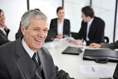 Senior businessman at a meeting laughing — Stock Photo