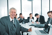 Senior businessman at a meeting. Group of colleagues in the background — Stock Photo