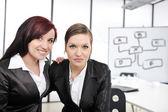 Portret van twee vrouwelijke ondernemers in bedrijfspresentatie op kantoor — Stockfoto