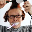 Senior woman brushing teeth and drying hair — Stock Photo