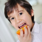 Child eating fresh orange fruit — Stock Photo