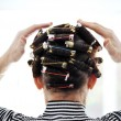 Woman with curlers on hair, back — Stock Photo