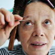 Stock Photo: Senior female tweezing eyebrow