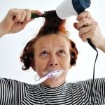 Senior woman brushing teeth and drying hair — Stock Photo #26252317