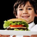 Little boy offering a hamburger on plate — Stock Photo #26252881