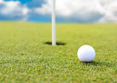 Golf ball at hole on grass field — Stock Photo