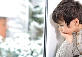 Sad kid on window cannot go out because of cold and snow — Stock Photo