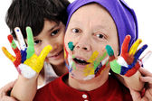 Parenting with little son playing with messy colors — Stock Photo