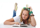 Female teenager laying and reading book — Stock Photo