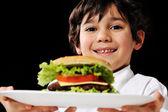 маленький мальчик, предлагая гамбургер на плите — Стоковое фото