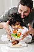 Hamburguesa levitando en aire de padre e hijo — Foto de Stock