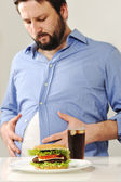 Fat man concerns about fast junk food — Stock Photo