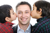 Two sons kissing father — Stockfoto