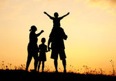 Happy family in nature at sunset — Stock Photo