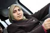 Arabic Muslim woman driving car wearing traditional scarf — Stock Photo