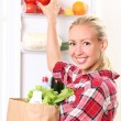 Young woman is putting a food into the fridge - Stock Photo