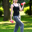 Woman working out with dumbbells in the park - 